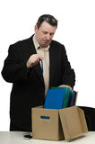 A man laid off from work. Middle aged man laid off from work place, is carrying his belongings into office box Royalty Free Stock Photos