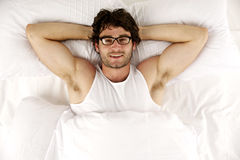 Man laid in white bed looking up at the camera smiling Stock Image