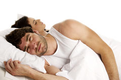 Man laid in white bed next to a sleeping woman Stock Photos