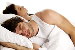 Man laid in white bed next to a woman sleeping Royalty Free Stock Images