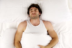Man laid in white bed sleeping. Handsome man laid sleeping enjoying a lie-in in the morning in a white bed Royalty Free Stock Photos