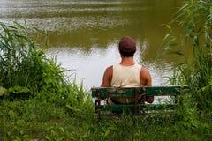 Man on lake. Man is sitting on bench on lake Royalty Free Stock Photos