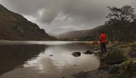 Man by lake. Man standing by a lake in wales uk royalty free stock photography