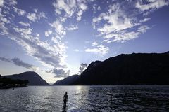 A man in a lake. A man in the lake of Lugano in Italy, at nightfall Royalty Free Stock Images