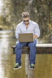 Man at the lake with notebook. An image of a bearded man at the lake with a notebook Royalty Free Stock Image