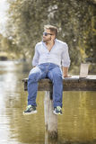 Man at the lake with notebook. An image of a bearded man at the lake with a notebook Stock Photography