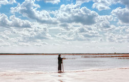 Man By The Lake Among Quartz Sand Under Beautiful Cloudy Sky. A man by the lake among the reeds in a quartz sand quarry with a distant horizon and a beautiful Royalty Free Stock Image
