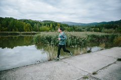 Man at the lake running against green cloudy nature. Man on the path at the lake running against green cloudy nature Royalty Free Stock Photos
