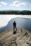 Man by a lake. Man in silhouette standing by a lake With melting ice Royalty Free Stock Photos