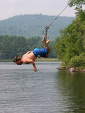 Man on a lake swing. Man in motion jumping into water from a New England traditional lake swing Royalty Free Stock Photos