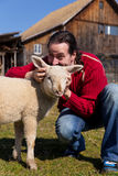 Man and lamb and a farmhouse Royalty Free Stock Photos