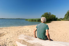 Man in landscape with river. Senior man sitting at tree trunk in landscape with river stock image