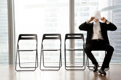 Man languishes while waits for turn on interview. Office worker covering face with sheet of paper when boring while waiting for meeting in office reception. Job stock photos