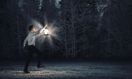 Man with lantern Stock Images