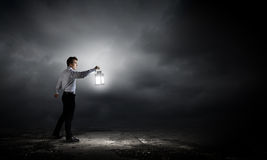 Man with lantern. Young handsome businessman walking in darkness with lantern Royalty Free Stock Images