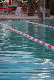 A man lap swims in an outdoor pool. A man in a red swim cap swims in an outdoor pool between the red and white lane markers as chairs and red umbrellas are ready royalty free stock photos