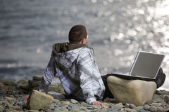 Man with laptop. Meditating on beach Royalty Free Stock Photos