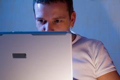 Man With Laptop. Man in casual dress using a laptop.  Face is partially obscured by laptop.  Multicolor lighting and blue cast used for effect Royalty Free Stock Photos
