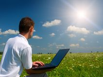 Man with laptop. In the green field royalty free stock photos