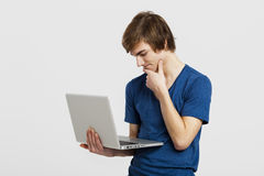 Man with a laptop. Handsome young man holding and working with a laptop, isolated over a white background Stock Image