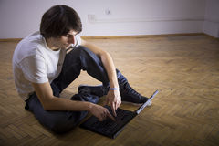Man with laptop. Casual young man on wooden floor with laptop Stock Image