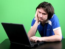 Man and laptop. Emotional man in blue t-shirt narrowly look to the display of deep gray laptop with green background Stock Image
