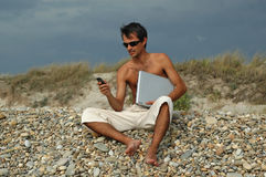 Man with laptop. A young man sited on the beach working with a laptop and with mobile phone Royalty Free Stock Photography
