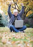 Man with laptop. Young college student raises both hands up in the air as he looks down at his laptop as he sits in the middle of the park in october Stock Photo