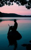 Man with laptop. Sitting on a rock on a lake Stock Photo