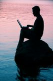 Man with laptop. Sitting on a rock on a lake Stock Images
