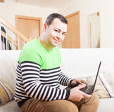 Man with laptop. Adult man sitting at his laptop at home royalty free stock photo