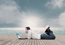 Man With Laptop. Asian Man Using Laptop On The Beach,Dramatic Look Royalty Free Stock Photography