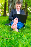 Man with laptop with bare feet Stock Photography