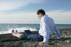 Man with laptop on the beach Royalty Free Stock Photos