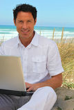 Man with laptop on beach Stock Image
