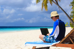 Man with laptop on beach vacation Stock Images