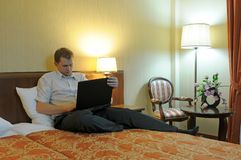 Man with laptop on bed Stock Photos