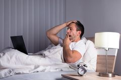 Man with laptop on bed yawning Stock Photos