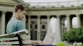 Man with laptop on a bench stock video footage