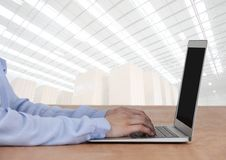 Man on laptop with bright warehouse background Stock Photos