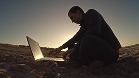 Man laptop businessman freelancer working behind sitting on beach freelancing silhouette in the sun