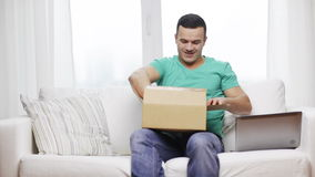 Man with laptop and cardboard box at home stock video