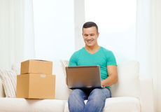 Man with laptop and cardboard boxes at home royalty free stock images