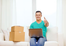 Man with laptop and cardboard boxes at home Stock Images