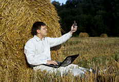 Man with laptop and cell phone. Business man with laptop at the field Royalty Free Stock Photography