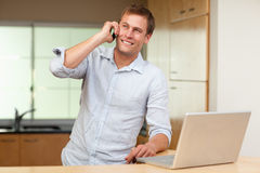 Man with laptop and cellphone in the kitchen Stock Photos