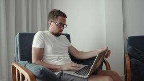 Man with laptop in chair. Close-up of a guy in glasses opens laptop at home sitting in a comfy chair. Typing on laptop stock video