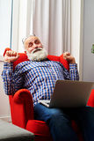 Man with laptop on the chair at home Stock Photography