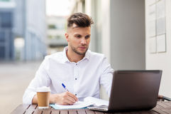 Man with laptop and coffee at city cafe Stock Image