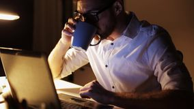 Man with laptop and coffee working at night office stock footage